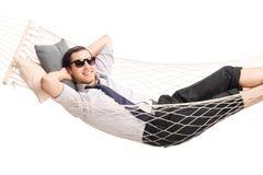 Homem de negócios novo despreocupado que encontra-se em uma rede Imagens de Stock