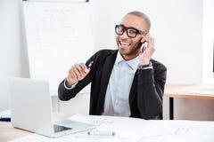 Homem de negócios novo que fala no telefone celular e que olha a câmera Imagem de Stock
