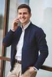 Homem de negócios novo que fala no telefone celular fora Imagem de Stock Royalty Free