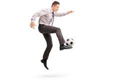 Homem de negócios novo que joga o futebol Fotos de Stock