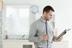 Homem de negócios novo que lê a notícia Fotografia de Stock Royalty Free