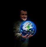 Homem de negócios novo que realiza no seu a mão um globo de incandescência da terra Fotografia de Stock