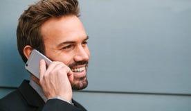 Homem de negócios novo Talking pelo telefone Fotos de Stock Royalty Free