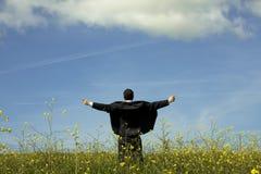 Homem de negócios outstretched em um campo Imagens de Stock Royalty Free