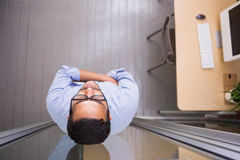 Homem de negócios pensativo que está contra a parede de vidro no escritório Imagem de Stock Royalty Free