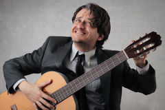 Homem de negócios que ajusta a guitarra Fotos de Stock