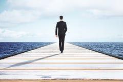 Homem de negócios que anda em uma estrada reta ao horizonte Fotos de Stock Royalty Free