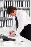Homem de negócios que classifica o papel Fotos de Stock Royalty Free