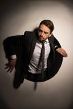 Homem de negócios que escala fora de um furo circular Fotografia de Stock