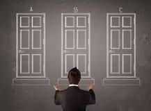 Homem de negócios que escolhe a porta direita Imagem de Stock Royalty Free