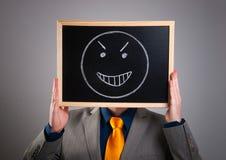 Homem de negócios que esconde sua cara com um quadro de avisos branco com um mal f Foto de Stock