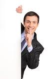 Homem de negócios que gesticula o silêncio, atrás do painel branco Foto de Stock Royalty Free