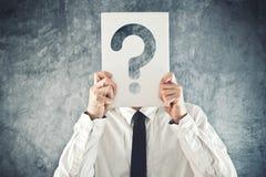 Homem de negócios que guarda de papel com ponto de interrogação impresso Imagens de Stock Royalty Free