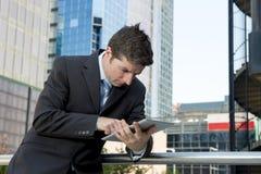 Homem de negócios que guarda a tabuleta digital que trabalha fora fora o distrito financeiro Fotografia de Stock Royalty Free