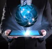 Homem de negócios que guarda a tabuleta digital sobre o globo Imagem de Stock