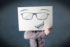 Homem de negócios que guardara um papel com a cara do smiley na frente de seu hea Imagem de Stock Royalty Free