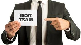 Homem de negócios que indica um cartão - a melhor equipe Imagem de Stock