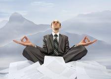 Homem de negócios que meditating nas montanhas Imagem de Stock Royalty Free