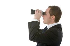 Homem de negócios que olha através dos binóculos Imagens de Stock