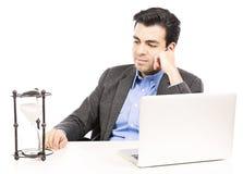 Homem de negócios que olha o vidro da hora Foto de Stock