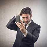 Homem de negócios que olha seu smartphone Fotografia de Stock Royalty Free