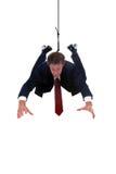 Homem de negócios que pendura por uma corda para placemen do produto Fotos de Stock Royalty Free
