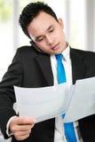 Homem de negócios que prende um relatório Imagens de Stock