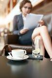 Homem de negócios que senta-se na entrada do hotel usando o telefone celular e o portátil Fotografia de Stock Royalty Free