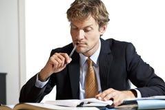 Homem de negócios que tenta figurar para fora o trabalho Imagens de Stock Royalty Free