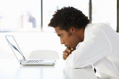 Homem de negócios Sitting At Desk no escritório que olha fixamente no portátil Fotografia de Stock Royalty Free