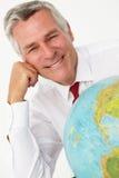 Homem de negócios sênior com globo Fotos de Stock Royalty Free