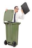 Homem de negócios terrificado que esconde em um balde do lixo Fotografia de Stock