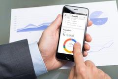 Homem de negócios Using Google Analytics no iPhone 6 de Apple Fotografia de Stock Royalty Free