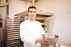 Homem de olhos escuros novo que sente o funcionamento feliz na padaria agradável foto de stock