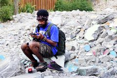 Homem de Papua que verifica para fora seu telefone celular imagens de stock