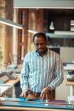 Homem de pele escura que faz algumas medidas antes de imprimir fotografia de stock royalty free