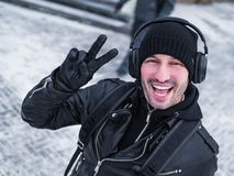 Homem de Pozitive no walkink dos fones de ouvido na rua no tempo de inverno Fotos de Stock Royalty Free