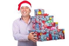 Homem de riso com os presentes da preensão do chapéu de Santa Imagens de Stock Royalty Free