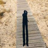 Homem de salto da sombra alongada em uma passagem de madeira Imagens de Stock