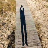 Homem de salto da sombra alongada em uma passagem de madeira Foto de Stock Royalty Free