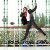 Homem de salto de sorriso com telefone móvel Fotografia de Stock Royalty Free