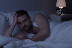 Homem de Slepless acordado na cama fotos de stock royalty free
