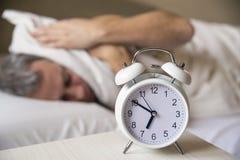 Homem de sono perturbado no amanhecer do despertador foto de stock