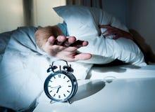 Homem de sono perturbado pelo mornin adiantado do despertador imagens de stock