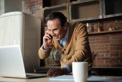 Homem de sorriso atrativo que olha seu computador Imagem de Stock Royalty Free