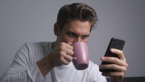 Homem de sorriso atrativo que usa o smartphone que envia a mensagem em meios sociais e que bebe o caf? interno filme