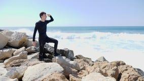Homem de sorriso caucasiano novo que olha o oceano com m?os para dirigir e que aponta o dedo ao horizonte ao estar no r vídeos de arquivo