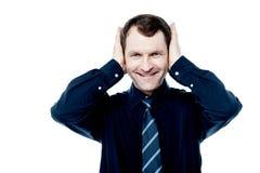 Homem de sorriso com mãos em suas orelhas imagens de stock royalty free