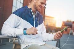 Homem de sorriso com o telefone celular e os auriculares que sentam-se no banco fora fotos de stock royalty free