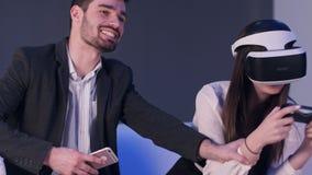 Homem de sorriso com o telefone que tenta confundir seu sócio fêmea de jogar o jogo da realidade virtual Fotografia de Stock
